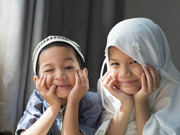 Closed up shot of asian muslim kids.young sister and brother sibling in muslim traditional dress.happy and looking to camera.concept of happy kid in ramadan or family bonding.