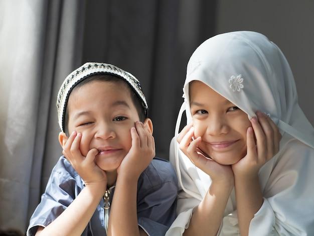 아시아 무슬림 kids.young 여동생과 무슬림 전통 드레스 형제 형제의 총을 닫았다. 행복하고 카메라를 찾고. 라마단 또는 가족 유대에서 행복한 아이의 개념.