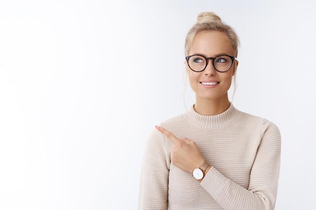 Крупным планом - красивая кавказская белокурая женщина в очках и свитере, чувствующая себя творческой и продуктивной, указывая в левый верхний угол, улыбается, мечтает, думает на белом фоне