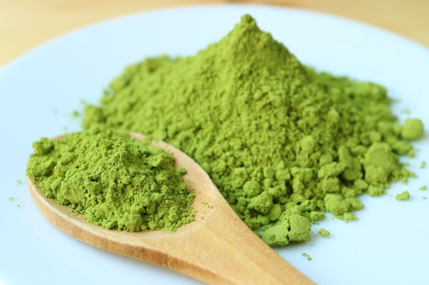 Closed up a spoon of vibrant green matcha tea powder on a plate with blurry green tea powder pile in background