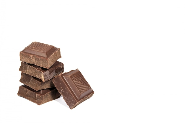 Closed up stack of dark chocolate cubes isolated on white background