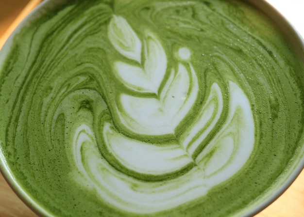 Closed up texture of hot japanese matcha green tea latte with latte art