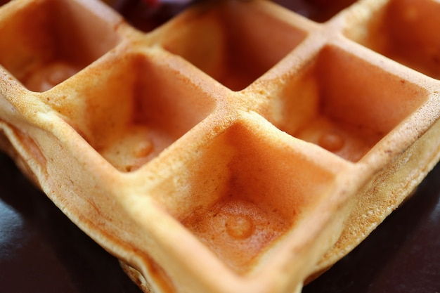 Closed up the texture of a tasty square shaped waffle on a black plate