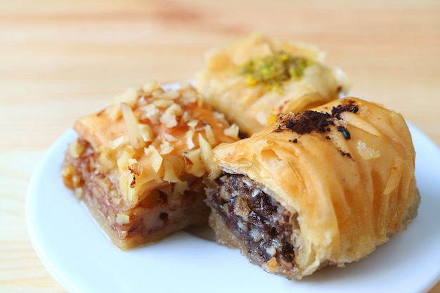 Closed up three types of baklava sweets on white plate served on wooden table