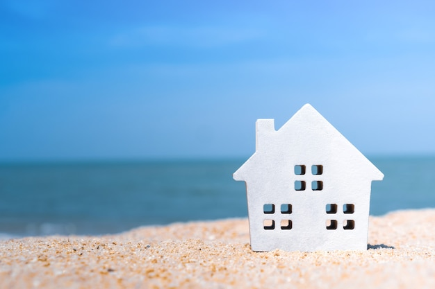 햇빛과 해변 배경으로 모래에 작은 집 모델을 올렸습니다.