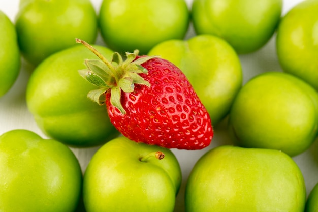 A closed up top view green cherry-plum round isolated sour fresh mellow with single strawberry on the white background fruit quality