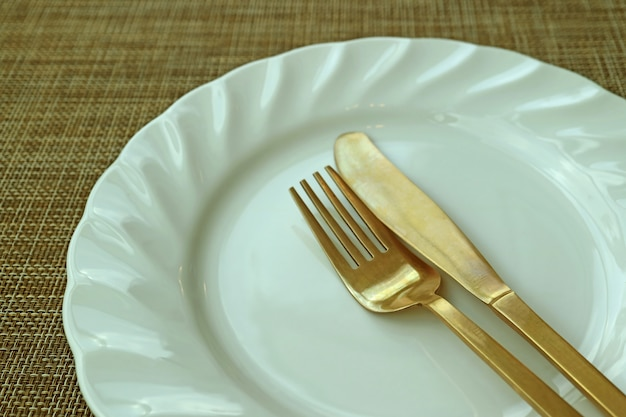 Closed up white ceramic plate and brass cutlery on beige luncheon mat