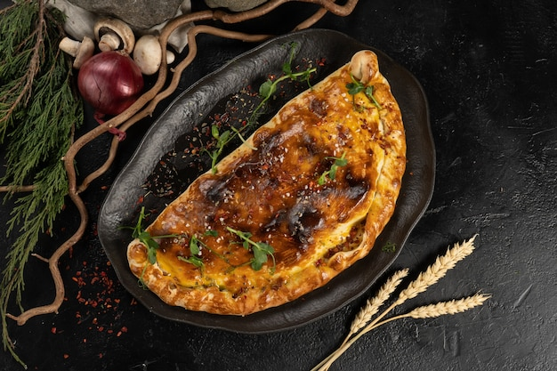 Closed vegetarian pizza calzone on a black plate