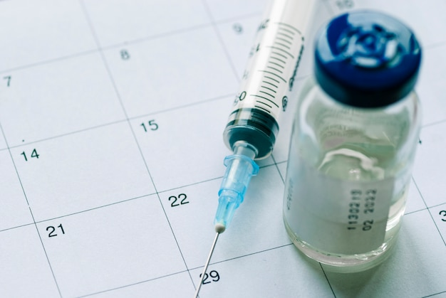 Closed vial with vaccine and empty syringe
