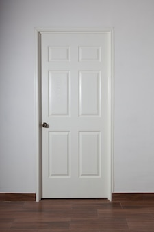 Closed white door on gray wall