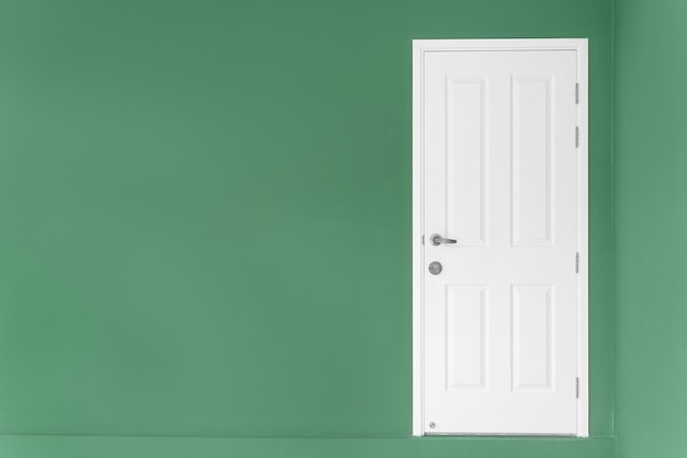 Closed white door on green wall at home.
