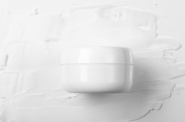 Closed white jar of face cream on a background of smeared cream