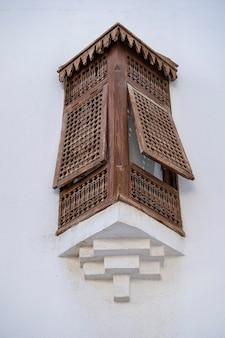 샤름 엘 셰이크(sharm el sheikh)에 있는 이집트 거리에 있는 오래된 흰 벽에 나무 막대가 있는 닫힌 창문이 닫혀 있습니다.