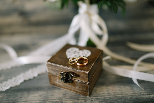 Закрытая деревянная шкатулка с сердечком и золотыми кольцами для жениха и невесты.