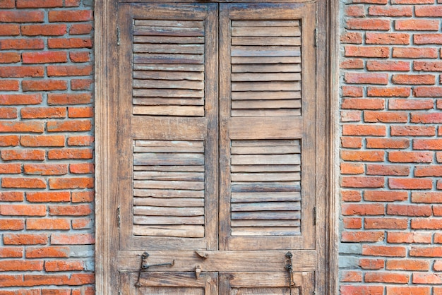 Closed wooden door with red bricks wall in old vintage house.