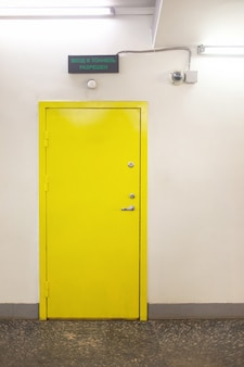 Закрытая желтая дверь на белой стене знак под дверью гласит, что вход в туннель разрешен