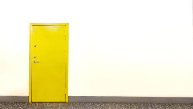 Закрытая желтая дверь на белой стене