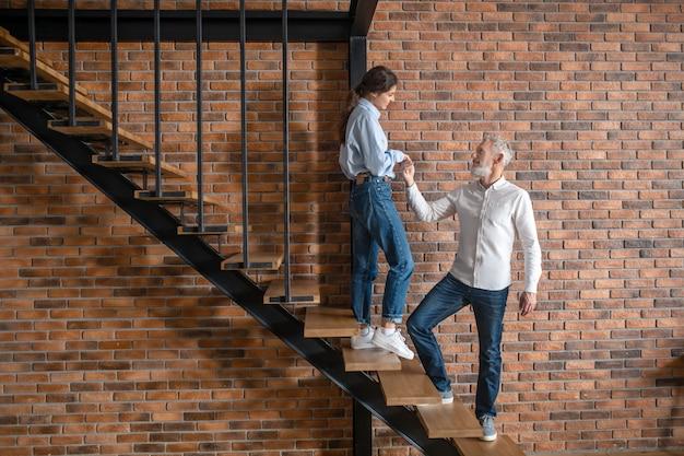 근사. 계단에 서서 서로를 바라보는 남자와 여자