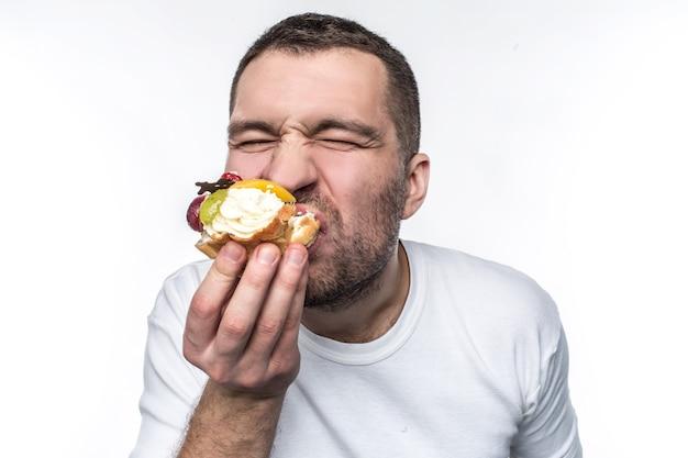 건강에 해롭고 단 음식을 많이 먹는 기이하고 이상한 남자의 클로즈업 샷. 그는 이 크림 같은 디저트를 먹고 있다. 흰색 배경에 고립