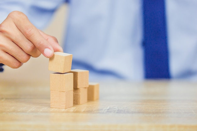 Closer up hands of businessmen,stacking wooden blocks into steps