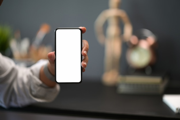 Closes up man showing blank screen mobile phone at creative workspace