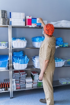 Closet with shelves of various medical equipment and supplies at a hospital. sanitizer. stocked shelves of medical scrubs. assistant chooses stuff.