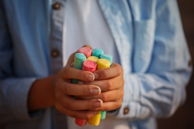 Closeuop childs hands holding colored chalks for drawing.