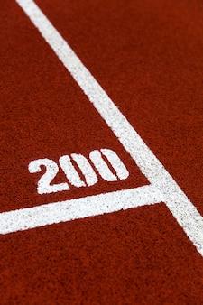 Closeup of the 200 mark on red stadium running track