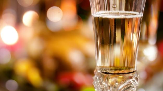 Крупным планом кадры 4k пузырьков воздуха, поднимающихся в бокале шампанского на фоне ярких огней на елке