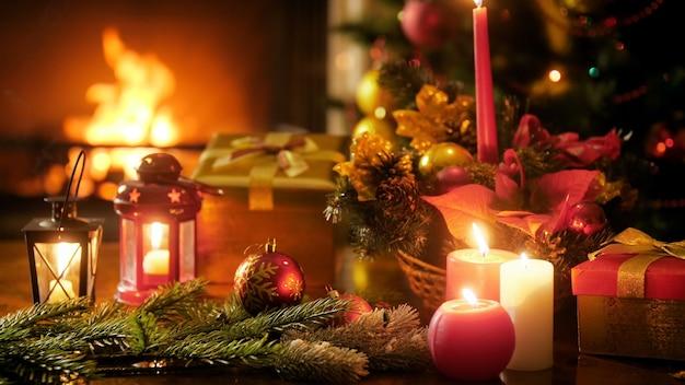 Крупным планом кадры 4k горящего камина в гостиной и красивый стол, украшенный свечами, безделушками и рождественскими подарками и подарками. идеальный снимок для зимних праздников и праздников