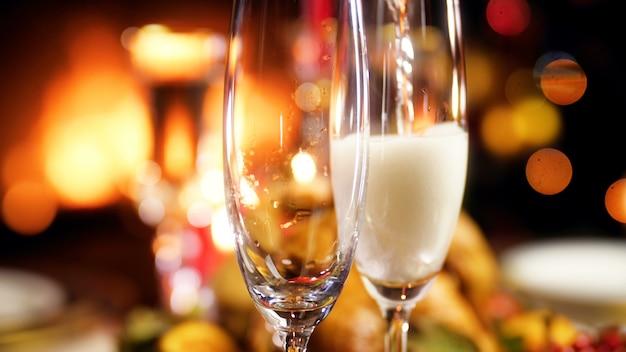 Крупный план 4k кадры наполнения двух бокалов газированным шампанским на фоне горящего камина и светящихся огней рождественской елки. обеденный стол для большой семьи на зимних праздниках и торжествах.