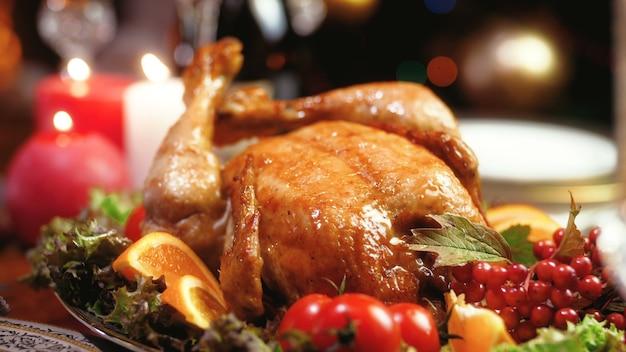 Крупным планом кадры 4k свежеиспеченного цыпленка, горящих свечей и светящихся рождественских огней на деревянном столе в гостиной. обеденный стол служил для большой семьи на зимних праздниках и торжествах.