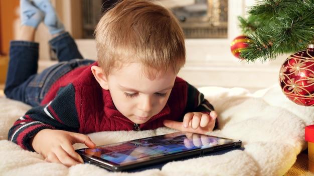 Крупным планом кадры 4k улыбающегося маленького мальчика, играющего в игры на цифровом планшетном компьютере, лежа под деревом christams дома. ребенок веселится на зимних праздниках и торжествах.