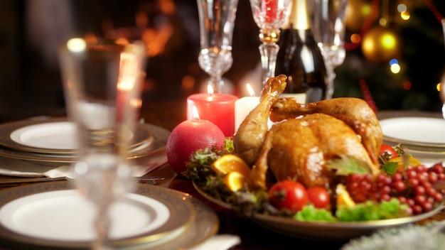 Крупным планом кадры 4k вкусной горячей свежеиспеченной курицы на большой богато украшенной тарелке. обеденный стол для большой семьи на зимних праздниках и торжествах.