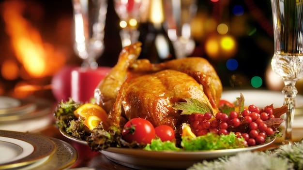 Крупным планом кадры 4k вкусного жареного цыпленка на большой тарелке против горящего камина и красочных рождественских огней. обеденный стол для большой семьи на зимних праздниках и торжествах.