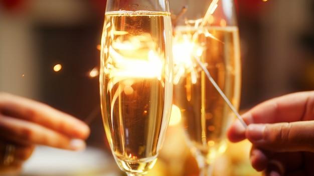 Closeup 4k кадры, на которых влюбленные молодой мужчина и женщина держат два горящих бенгальских огня на столе с бокалами шампанского. семья празднует рождество и новогодние праздники