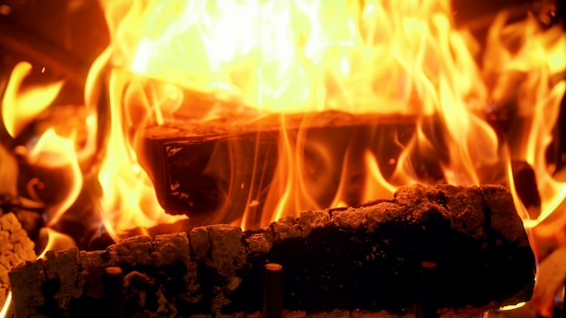 Closeup 4k footage of wooden logs burning in fireplace. flame and smoke rising up
