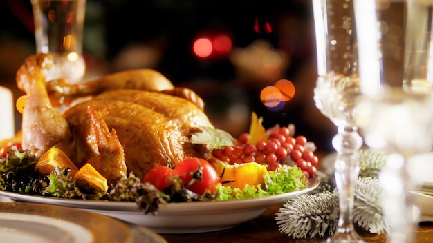 Крупным планом кадры панорамирования 4k запеченной индейки с овощами и бокалами, наполненными игристым шампанским. обеденный стол для большой семьи на зимних праздниках и торжествах.