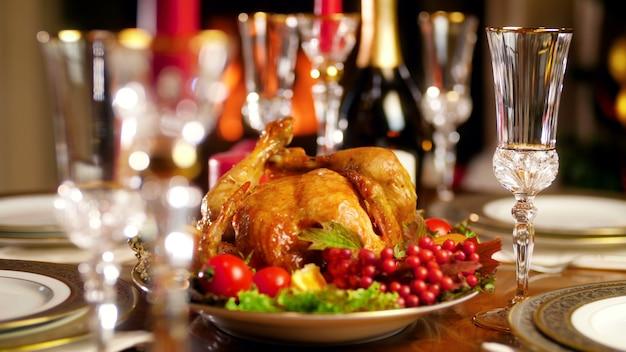 Крупным планом кадры панорамирования 4k красивого ужина в гостиной на фоне горящего камина и светящейся рождественской елки. обеденный стол для большой семьи на зимних праздниках и торжествах.