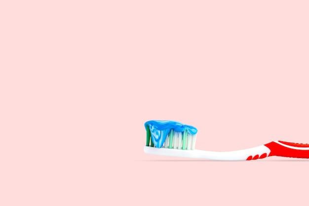 분홍색 배경에 격리된 칫솔에 파란색과 흰색 치약을 닫습니다.