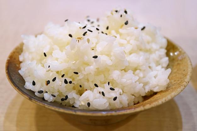참깨를 뿌린 갓 지은 일본 쌀 한 그릇