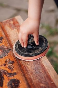 Крупным планом рука ребенка держит рулон с наждачной бумагой и прочесывает старый деревянный стол с цветочным деревом ...