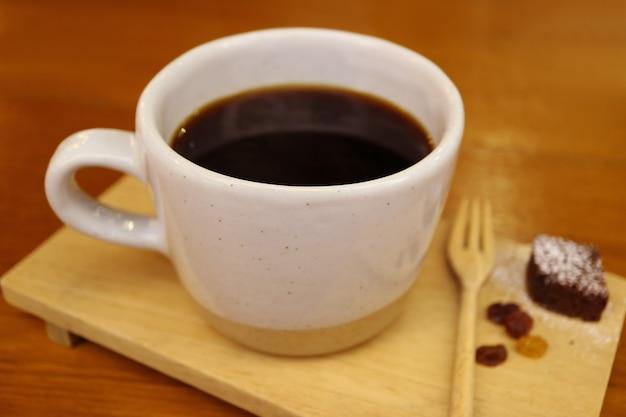 背景にぼやけたチョコレートとホットコーヒーのカップをクローズアップ