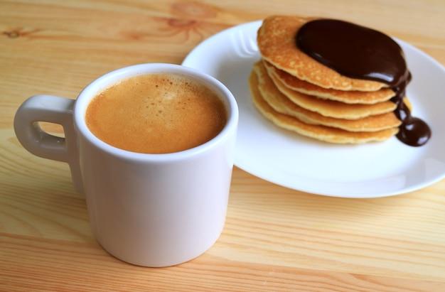 バックグラウンドでチョコレートガナッシュソースとぼやけたパンケーキとホットコーヒーのカップをクローズアップ