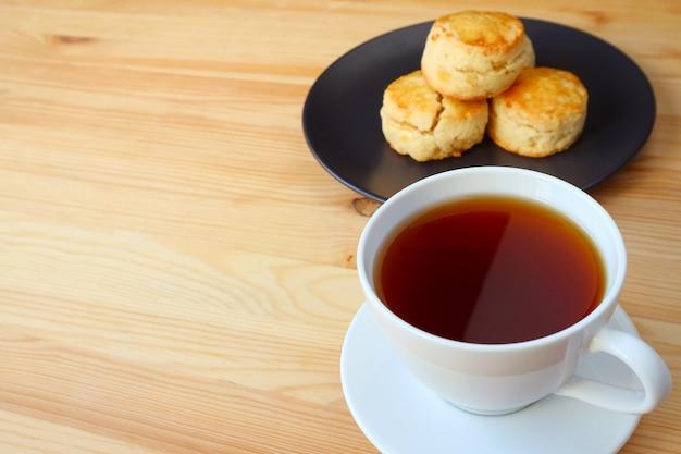 木製のテーブルで提供されるスコーンのプレートと熱いお茶のカップをクローズアップ
