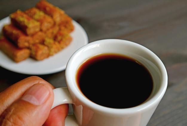背景にぼやけたバクラヴァペストリーと手にトルココーヒーのカップをクローズアップ