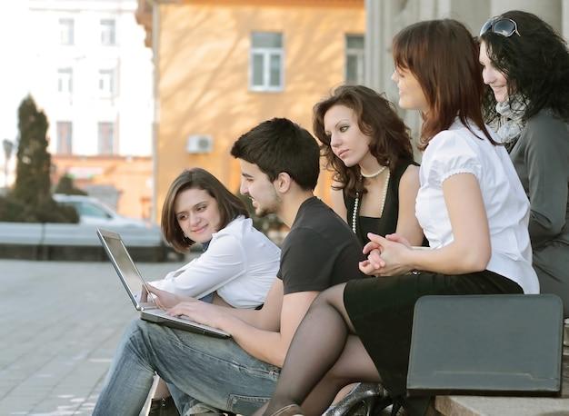 Крупным планом группа студентов, общающихся через интернет с помощью ноутбука