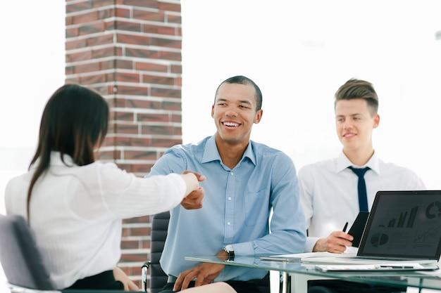 Крупным планом. рукопожатие менеджера и сотрудника в офисе.