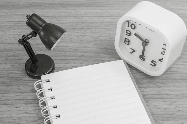 黒と白のトーンの木製の机のテクスチャ背景に小さなランプと白い目覚まし時計でメモ帳をクローズアップ