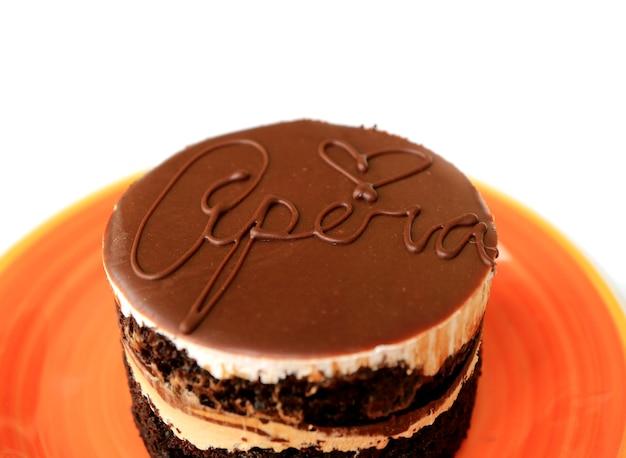 Крупным планом вкусный оперный торт круглой формы подается на ярко-оранжевой тарелке, изолированной на белом фоне
